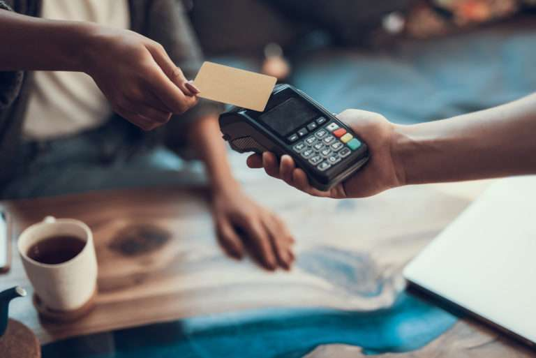 Hands of cafe visitor holding credit card and putting it to the card payment machine
