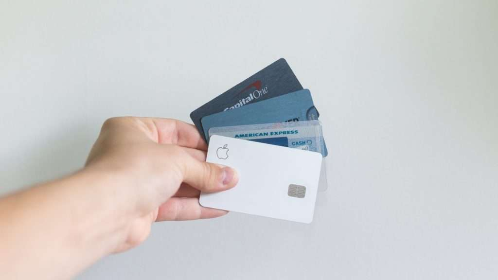 someone holding out 4 credit cards fanned out