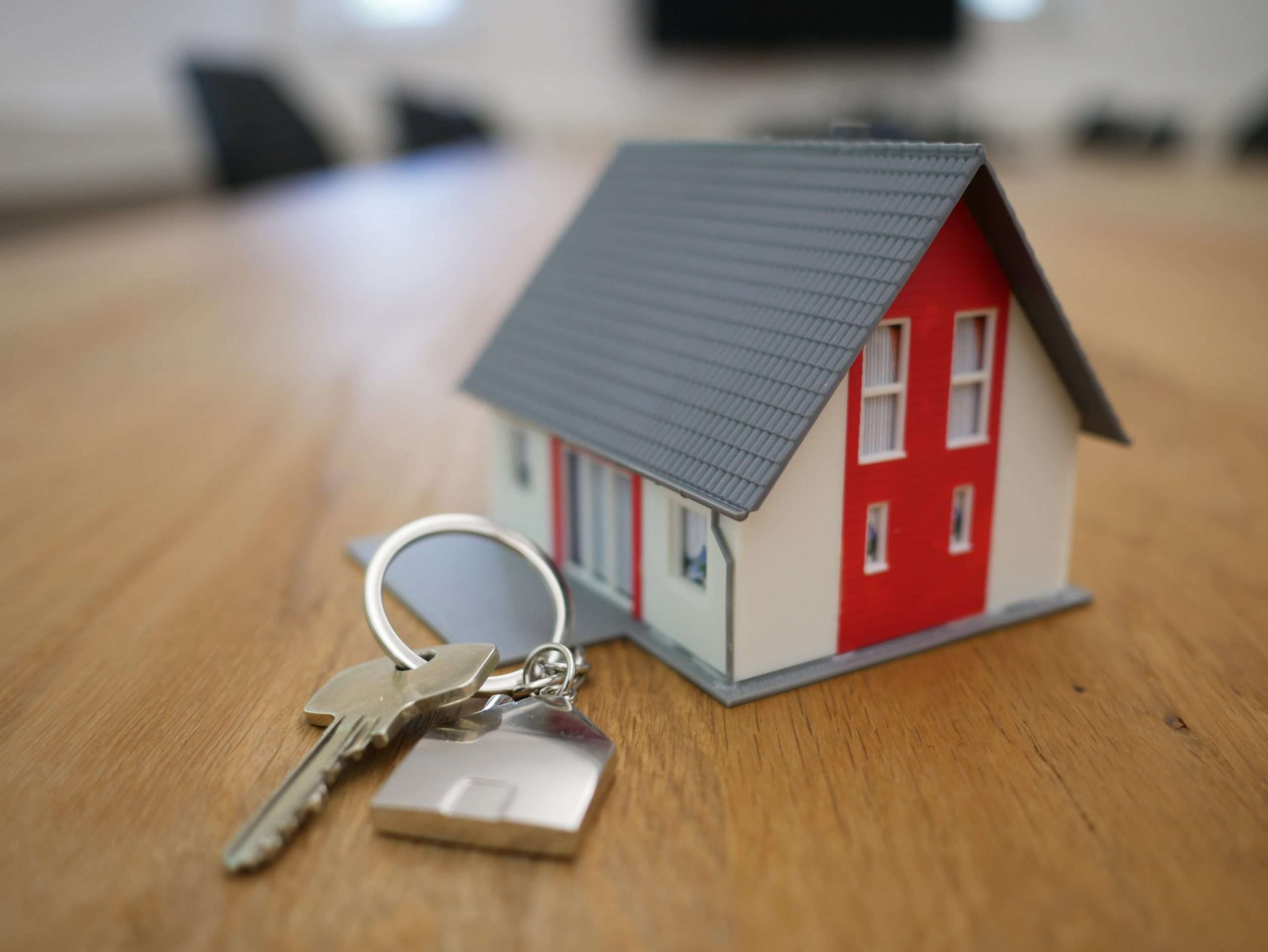 key chain with keys and a small house next to it